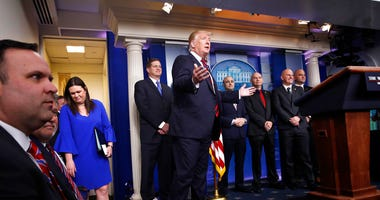 President Donald Trump gestures as he arrives in the press briefing room