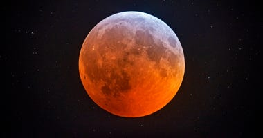 The totally eclipsed moon glows with a reddish color against the background stars