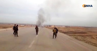 This frame grab from video provided by Hawar News, ANHA, the news agency for the semi-autonomous Kurdish areas in Syria, shows Kurdish fighters standing guard at the site of a suicide attack near the town of Shaddadeh, in Syria's northeastern province of