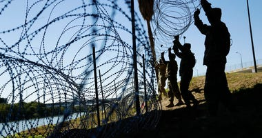 members of the U.S. military install multiple tiers of concertina wire along the banks of the Rio Grande near the Juarez-Lincoln Bridge at the U.S.-Mexico border, in Laredo, Texas.