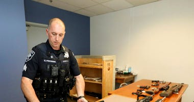 Seattle Police Crisis Response Team Sgt. Eric Pisconski displays guns seized from people deemed to be a danger to themselves or others