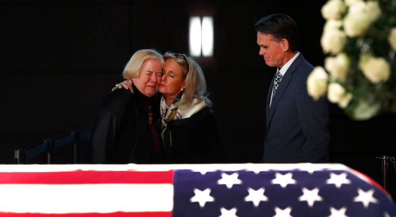 Rep. Debbie Dingell, D-Mich., center, consoles former Rep. Candice Miller, R-Mich., as Macomb County executive Mark Hackel, right, looks on at the casket of her husband and former Rep. John Dingell, lying in repose in Dearborn, Mich., Monday, Feb. 11, 201