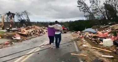 People walk amid debris in Lee County, Ala.