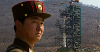 File Photo: A soldier stands in front of a rocket at a launching site in North Korea