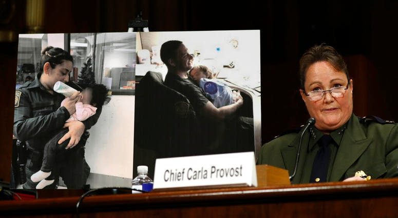U.S. Border Patrol Chief Carla Provost testifies by a photo of agents with children during a Senate Judiciary Border Security and Immigration Subcommittee hearing about the border, Wednesday May 8, 2019, on Capitol Hill in Washington.