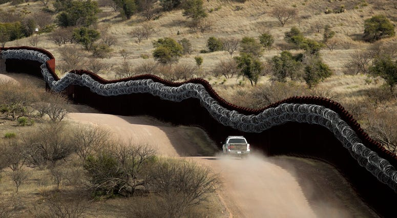 Customs and Border Control agent patrols on the US side of a razor-wire-covered border wall along the Mexico east of Nogales, Ariz