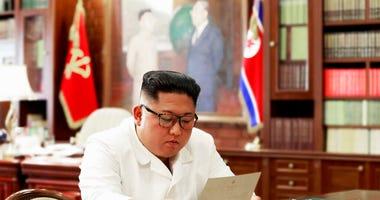 North Korean leader Kim Jong Un reads a letter from U.S. President Donald Trump