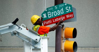 """A worker hangs a street sign before a ceremony honoring singer Patti LaBelle, Tuesday, July 2, 2019, in Philadelphia. A stretch of Broad Street, between Locust and Spruce Streets, will be renamed """"Patti LaBelle Way."""""""