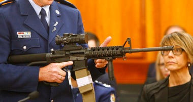 Police Sr. Sgt. Paddy Hannan shows New Zealand lawmakers an AR-15 style rifle