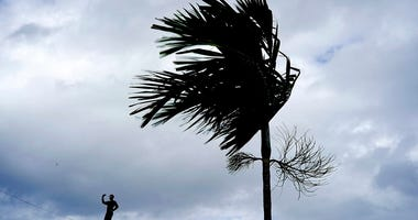 A man stands on a store's roof as he works to prepare it for the arrival of Hurricane Dorian in Freeport on Grand Bahama, Bahamas,