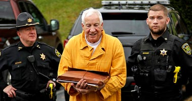 Former Penn State University assistant football coach Jerry Sandusky, center, arrives at the Centre County Courthouse
