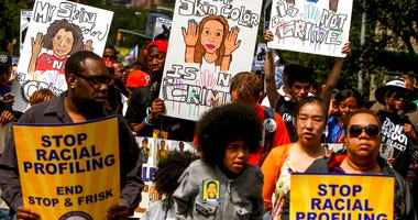 """protestors with signs during a silent march to end """"stop-and-frisk"""" program in New York. During the Bloomberg administration, civil rights groups went to court to end the NYPD's use of a tactic known as """"stop and frisk,"""" which involved detaining, question"""