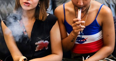 two women smoke cannabis vape pens at a party in Los Angeles. On Thursday, Dec. 12, 2019, U.S. health officials said 26 states have reported deaths, for a total of 52.