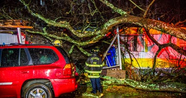 Cory Simpson of Decatur Fire & Rescue assess damage before evacuating a mobile home after a tree fell on the home in Decatur, Ala., Monday, Dec. 16, 2019.