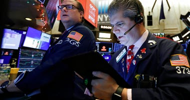 Gregg Maloney, left, and trader John Panin work on the floor of the New York Stock Exchange. The U.S. stock market opens at 9:30 a.m. EST on Thursday, Dec. 26.