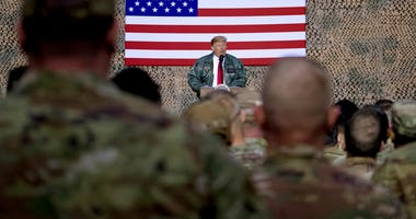 President Donald Trump speaks to members of the military at a hangar rally at Ain al-Asad air base, Iraq.
