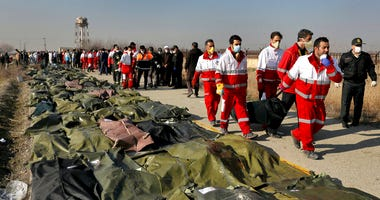 Rescue workers carry the body of a victim of a Ukrainian plane crash in Shahedshahr, southwest of the capital Tehran, Iran,