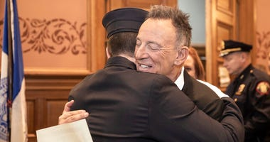 In this photo provided by the Jersey City Mayor's Office, Bruce Springsteen hugs his son Sam Springsteen