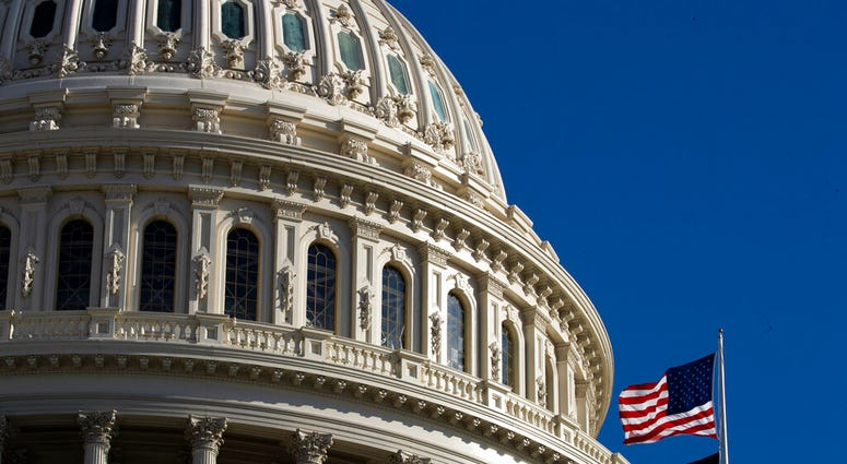 The U.S. flag flies over the U.S. Capitol in Washington, Sunday, Jan. 19, 2020.