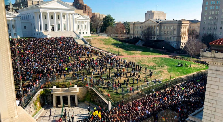 Demonstrators are seen during a pro-gun rally, Monday, Jan. 20, 2020, in Richmond, Va. Thousands of pro-gun supporters are expected at the rally to oppose gun control legislation like universal background checks that are being pushed by the newly elected