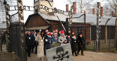 Poland's President Andrzej Duda walks along with survivors through the gates of the Auschwitz Nazi concentration camp to attend the 75th anniversary of its liberation in Oswiecim, Poland, Monday, Jan. 27, 2020.