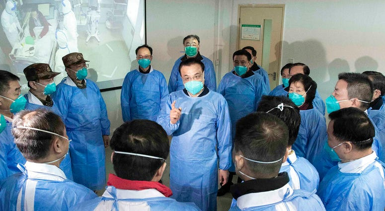 China's Xinhua News Agency, Chinese Premier Li Keqiang, center, speaks with medical workers at Wuhan Jinyintan Hospital in Wuhan in central China's Hubei province, Monday, Jan. 27, 2020.