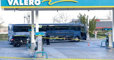 Investigators are seen outside of a Greyhound bus after a passenger was killed on board on Monday, Feb. 3, 2020