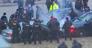 In this image take from video, law enforcement personnel surround a car after it was stopped as the driver approached the crowd near Union Station attending the Super Bowl parade and rally for the Kansas City Chief in Kansas City, Mo., Wednesday, Feb. 5,