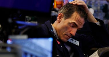 Trader Gregory Rowe prepares for the day's activity on the floor of the New York Stock Exchange, Monday, March 9, 2020. Trading in Wall Street futures has been halted after they fell by more than the daily limit of 5%.