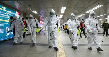 Workers wearing protective gears disinfect as a precaution against the new coronavirus at the subway station in Seoul, South Korea, Wednesday, March 11, 2020.