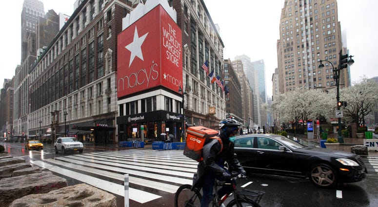 A cyclist passes Macy's in Herald Square, Monday, March 23, 2020, in New York. Macy's stores nationwide are closed due to the coronavirus.