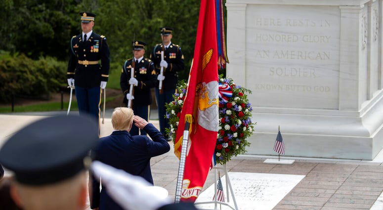 President Donald Trump salutes before placing a wreath at the Tomb of the Unknown Soldier in Arlington National Cemetery, in honor of Memorial Day, Monday, May 25, 2020, in Arlington, Va. (AP Photo/Alex Brandon)