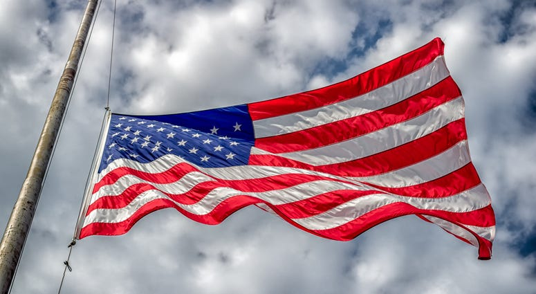 American flag at half-staff blowing in wind