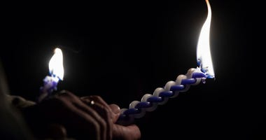 A vigil participant holds a Havdalah candle during a Havdalah vigil for the victims of the Tree of Life Congregation shooting