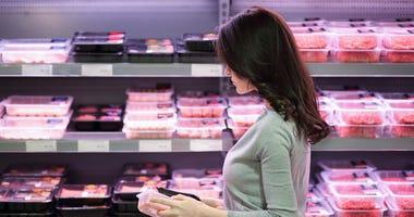 Woman choosing product in supermarket