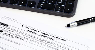 Application for employment benefits form with computer keyboard and pen on white background.