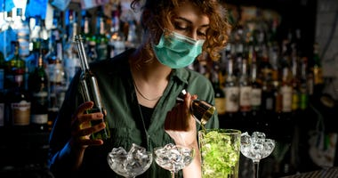 Young bartender girl in a medical mask pour green liquid from beaker into glass with ice.