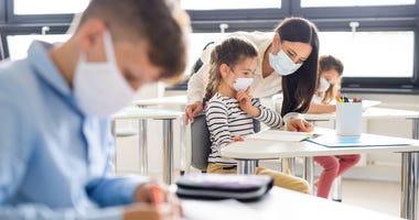 masked students and teacher during coronavirus pandemic