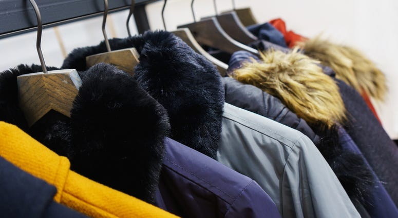 Modern outerwear in a shop on a hanger. Jackets, parks and warm outerwear of different colors and denim for youth.