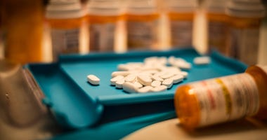 Unsorted prescription pills sit in a pharmacist's counting tray before they are bottled.