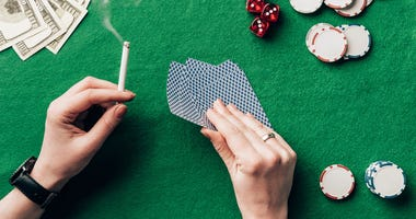 Woman holding cigarette and playing cards by casino table