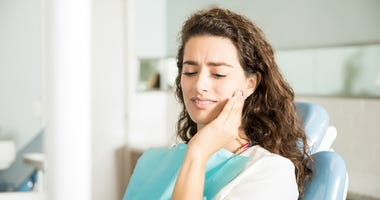 Young Woman Suffering From Toothache In Dental Clinic