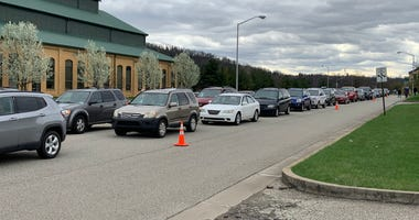 Cars line up for emergency food distribution on Monday, March 30, 2020