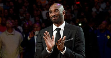 Kobe Bryant smiles at halftime as both his #8 and #24 Los Angeles Lakers jerseys are retired