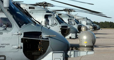A variety of different types of helicopters in the Navy and Marines inventory line the tarmac