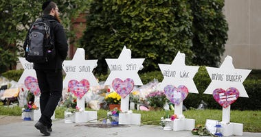 A man visits a memorial outside of the Tree of Life Congregation Synagogue in the Squirrel Hill neighborhood