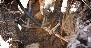 connects the new pipe with a test pipe as he works on lead pipe replacement