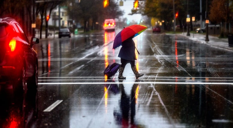 A pedestrian carries a colorful umbrella