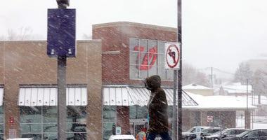 A pedestrian walks through snow