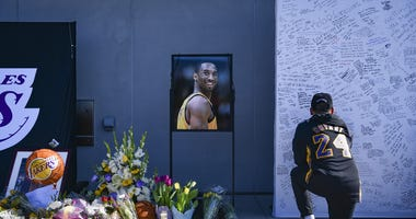 os Angeles residents and fans write notes and mourn the loss of Kobe Bryant in front of the Los Angeles Lakers practice facility.
